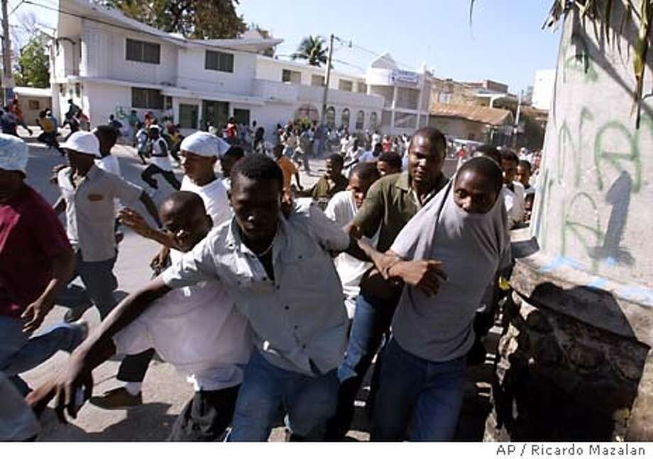 Opponents of ousted President Jean-Bertrand Aristide run away from shooting in Port-au-Prince, Haiti Sunday, March 7, 2004. Gunshots erupted Sunday at a protest to demand that ousted Haitian President Jean-Bertrand Aristide be tried for corruption and fomenting violence. At least four demonstrators and a foreign journalist were killed. (AP Photo/Ricardo Mazalan) Photo: RICARDO MAZALAN
