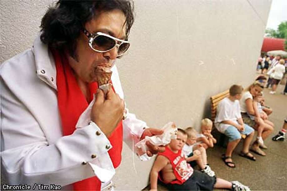 =VINCE Duke, an impersonator from Arkansas, munches on an ice cream as he waits to get into Graceland Sat. afternoon. He became elvis about a year ago. Before that he was in a rock and roll band for over 30 years. photo by tim Kao/the chronicle Photo: TIM KAO