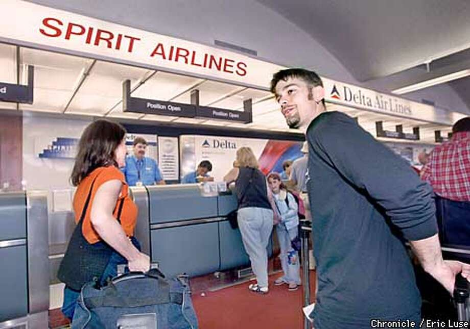 Jennifer Ardis and Dan Keaton, flying from Oakland to Detroit on Spirit Airlines, say they'd accept free tickets for Sept. 11. Chronicle photo by Eric Luse