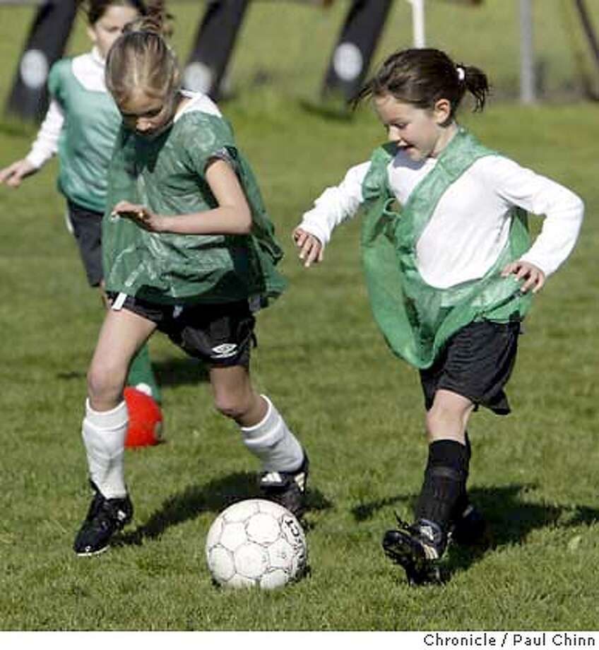 Grace Strausser (L) and Caroline Newman try to impress coaches evaluating their skills at the Lamorinda league tryouts. Tryouts for youth soccer teams on 3/6/04 in Moraga. PAUL CHINN/The Chronicle Photo: PAUL CHINN