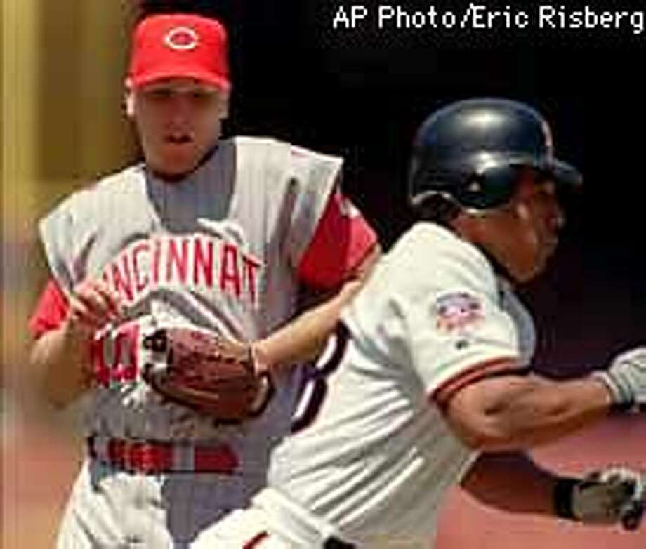 Cincinnati Reds starting pitcher Brett Tomko, left, attempts to tag San Francisco Giants' Stan Javier, who is running toward first base, during the second inning Tuesday, Aug. 12, 1997, in San Francisco. Tomko tossed an errant throw to first base, allowing Javier to advance to second base. (AP Photo/Eric Risberg) Photo: ERIC RISBERG