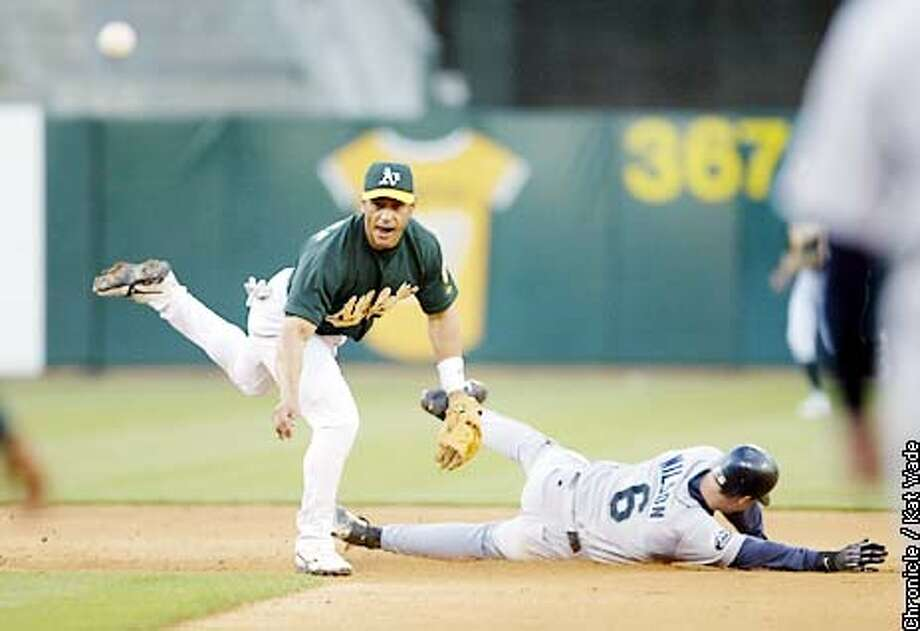 The Oakland Atheletic's #8 Randy Velarde takes the Seattle Mariner's #6 Dan Wilson out at second then throws taking Seattle's Jeff Cirillo out at first for a double play and third out in the second inning of the game against the Seattle Mariners at Network Associates Coliseum in Oakland. SAN FRANCISCO CHRONICLE PHOTO BY KAT WADE Photo: KAT WADE