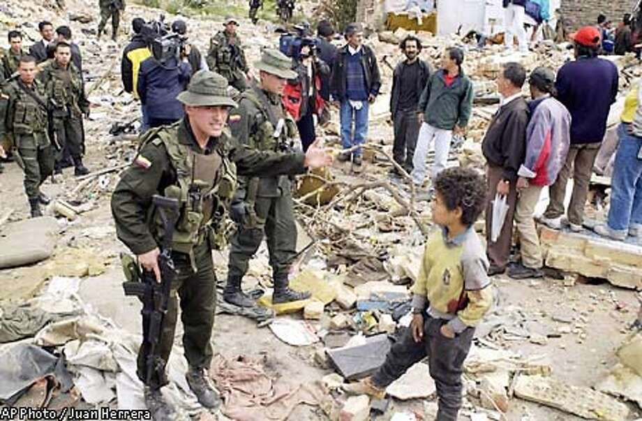 Police try to clear an area where an explosion occurred at the beginning of the inauguration ceremony for President Alvaro Uribe in Bogota, Colombia on Wednesday, Aug. 7, 2002. Explosions rocked Bogota and the presidential palace before and after the inauguration Wednesday of Uribe.(AP Photo/Juan Herrera) Photo: JUAN HERRERA