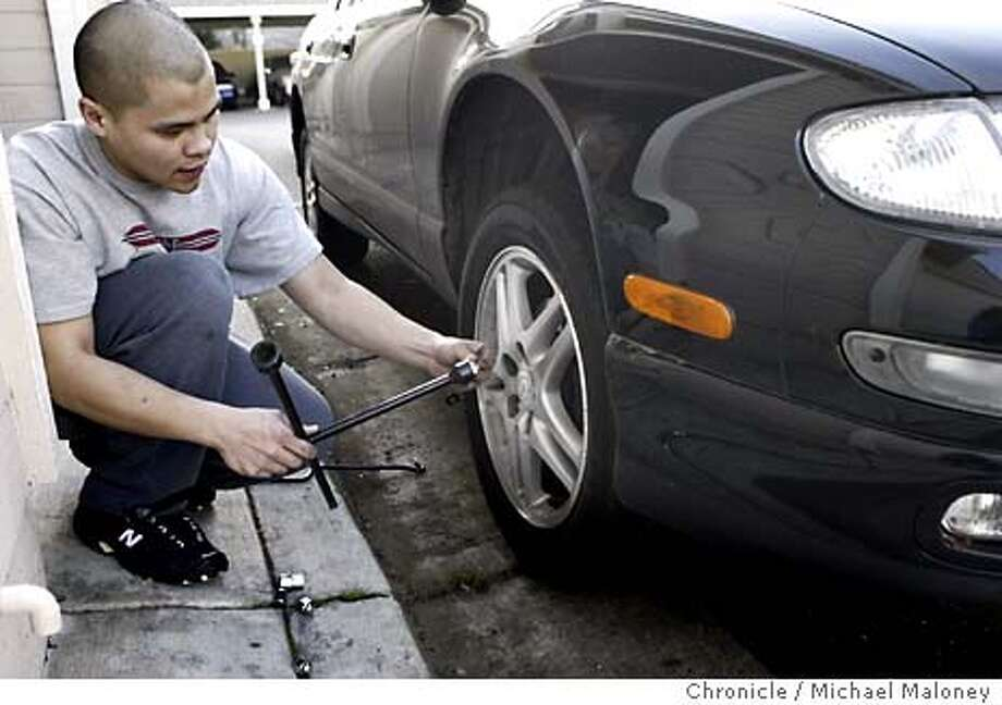"""Twenty three year old Dale Cuevas changes the rims on his car in preparation of moving back to the Philippines. He sold the more expensive rims to his cousin and now has to sell his car.  The Cuevas family of Fremont was given an order of """"voluntary departure"""" in December. They were given 70 days to leave the country and return to the Philippines. The family came to the U.S. as visitors in1985. They overstayed their visas and became illegal aliens. In 1997, they tried to legalize their status and now it's backfired on the family.  Event on 1/8/04 in Fremont.  Michael Maloney / The Chronicle Photo: Michael Maloney"""