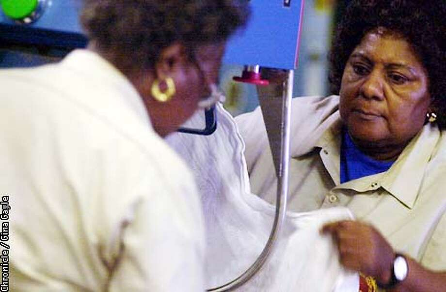Wilma King (back) and Melba Davis who have worked in the Laguna Honda Hospital's laundry service for 18 and 15 years respectively, load blankets onto a pressing machine. Photo by Gina Gayle/The SF Chronicle. Photo: GINA GAYLE