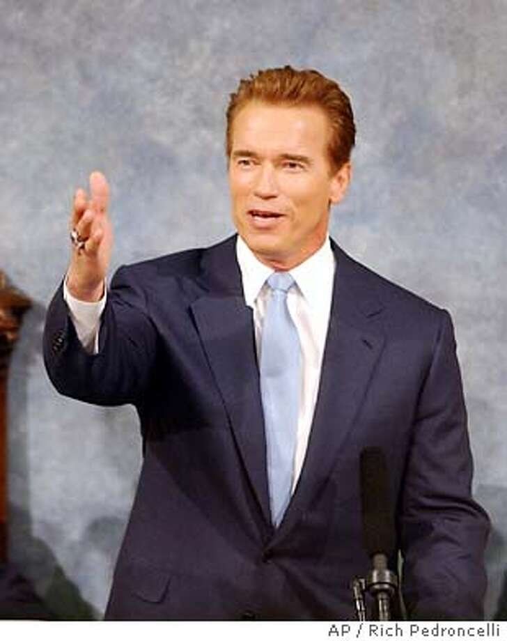 Gov. Arnold Schwarzenegger gestures to his wife, Maria Shriver, during his opening remarks of his first State of the State address held during a joint session of the Legislature at the Capitol in Sacramento, Calif., Tuesday, Jan. 6, 2004. In a turning point marking his transition from Hollywood idol to California's leader, Gov. Arnold Schwarzenegger focused his first major address Tuesday on a financial crisis he said would entail painful budget cuts. (AP Photo/Rich Pedroncelli) State of the State: Gov. Arnold Schwarzenegger addressing the Legislature.. Photo: RICH PEDRONCELLI