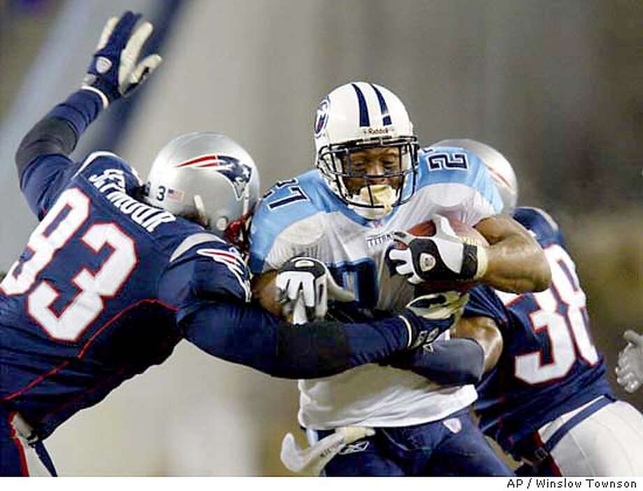 Tennessee Titans' Eddie George (27) is wrapped up by New England Patriots' Richard Seymour (93), left, and Tyrone Poole (38), right, in an attempted run in the third quarter of their AFC playoff game at Gillette Stadium, Saturday, Jan. 10, 2004, in Foxboro, Mass.. (AP Photo/Winslow Townson) Photo: WINSLOW TOWNSON