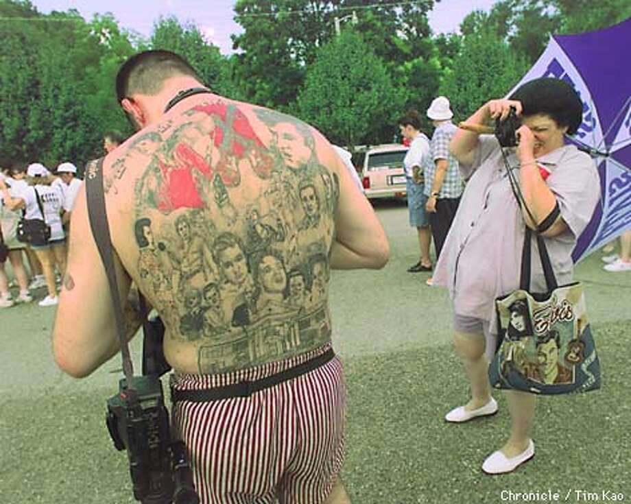 "=KEITH Eason of England has tattooed 18 faces of Elvis plus a Graceland on his back. This is his first time in Tupelo. He has been a fan for 23 years, since he was nine. Gina Klein of New Jersey snaps a picture of him. She has been a fan since ""forever"" and has been coming here since 85. photo by tim kao/the chronicle Photo: TIM KAO"