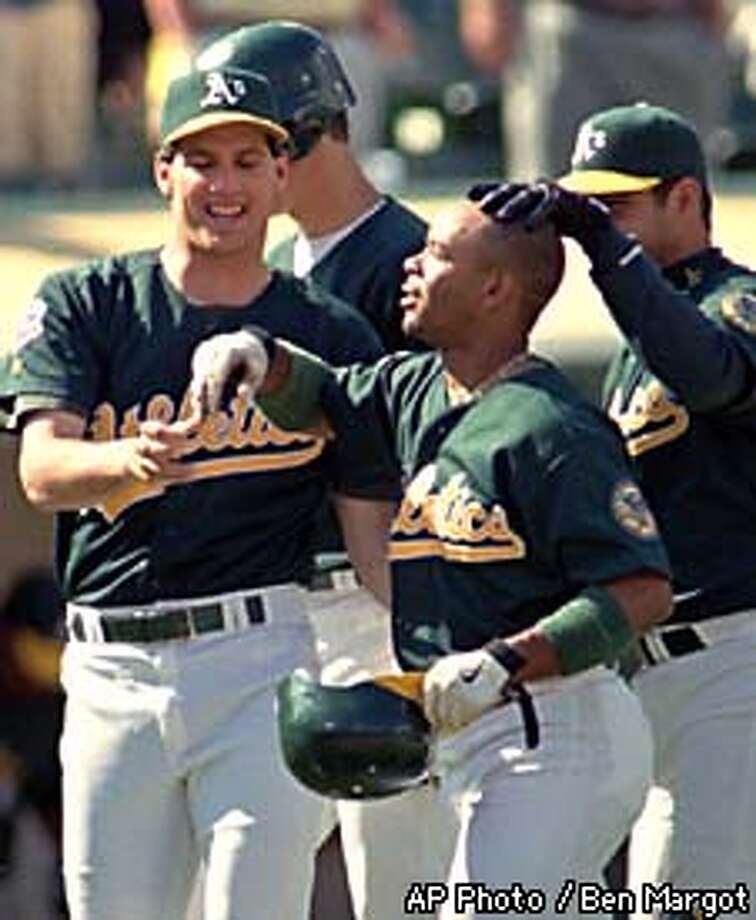 Oakland Athletics' Jason McDonald, holding his helmet, is welcomed by teammates after hitting the game-winning double in the bottom of the ninth inning against the Milwaukee Brewers Sunday, Aug. 10, 1997, at the Oakland, Calif., Coliseum. Oakland defeated Milwaukee in the first game of a double-header, 4-3. (AP Photo/Ben Margot) Photo: BEN MARGOT