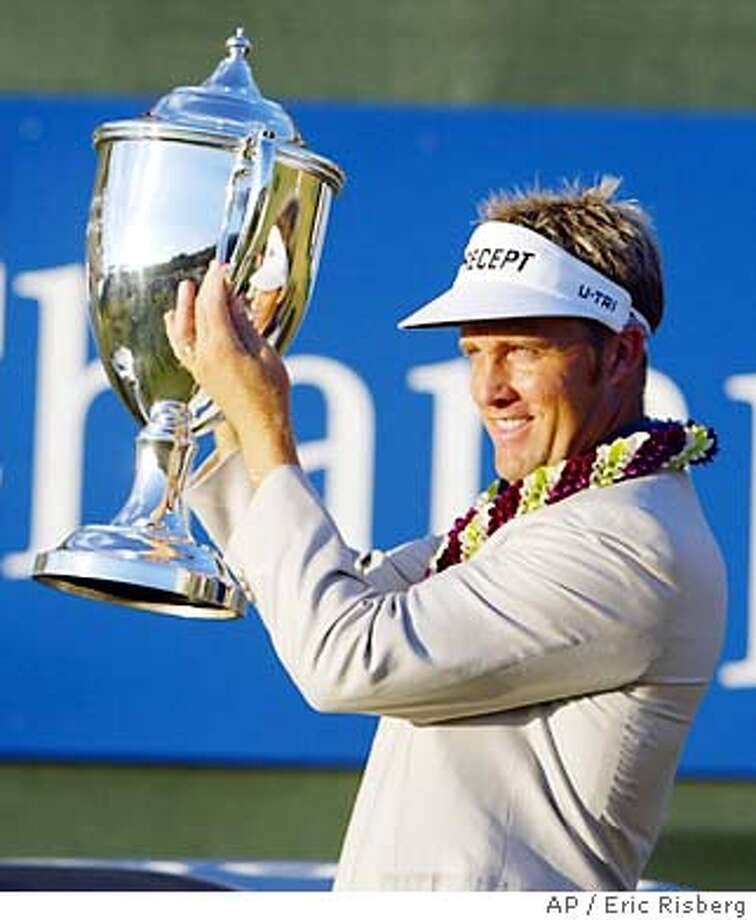 Stuart Appleby of Australia holds up his trophy on the 18th green of the Plantation Course after winning the Mercedes Championships in Kapalua, Hawaii Sunday Jan. 11, 2004. Appleby shot a 2-under-par 71 to finish at total 22-under-par.(AP Photo/Eric Risberg) Photo: ERIC RISBERG