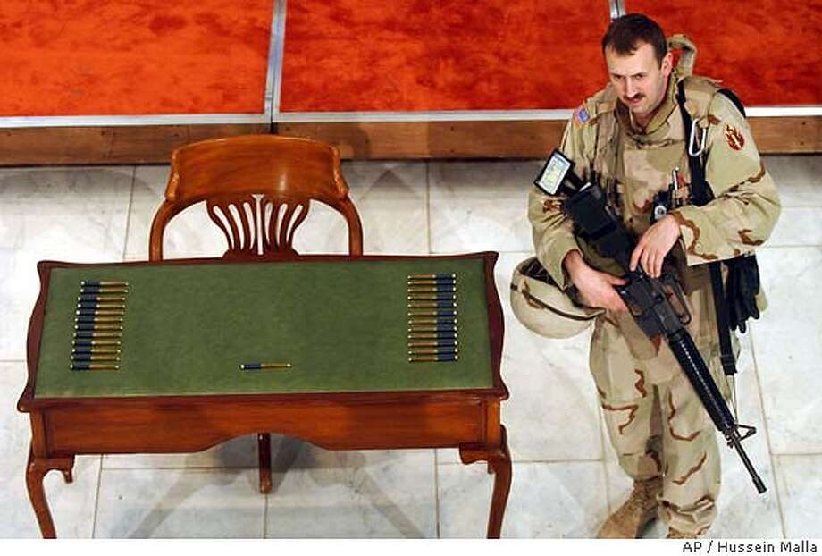 ** CORRECTED VERSION **A US soldier stands next to an empty chair and a table with 25 pens to be used by an equal number of members of the Iraqi Governing Council for the historic signing of the new Iraqi interim constitution on Friday March 5, 2004 in Baghdad, Iraq. The signing ceremony has been delayed for more than five hours now after Shiite leaders refused to sign an interim constitution following Iraq's top Shiite cleric rejection of portions of the charter in a dispute that marred a landmark in the U.S. plans to hand over sovereignty to the Iraqis. (AP Photo/Hussein Malla) CORRECTS PHOTOGRAPHER'S NAME TO HUSSEIN Photo: HUSSEIN MALLA