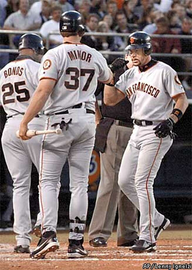 San Francisco Giants' Benito Santiago, right, is greeted by teammates Damon Minor and Barry Bonds (25) after his three-run homer during the third inning against the San Diego Padres Monday, June 3, 2002, in San Diego. (AP Photo/Lenny Ignelzi) Photo: LENNY IGNELZI
