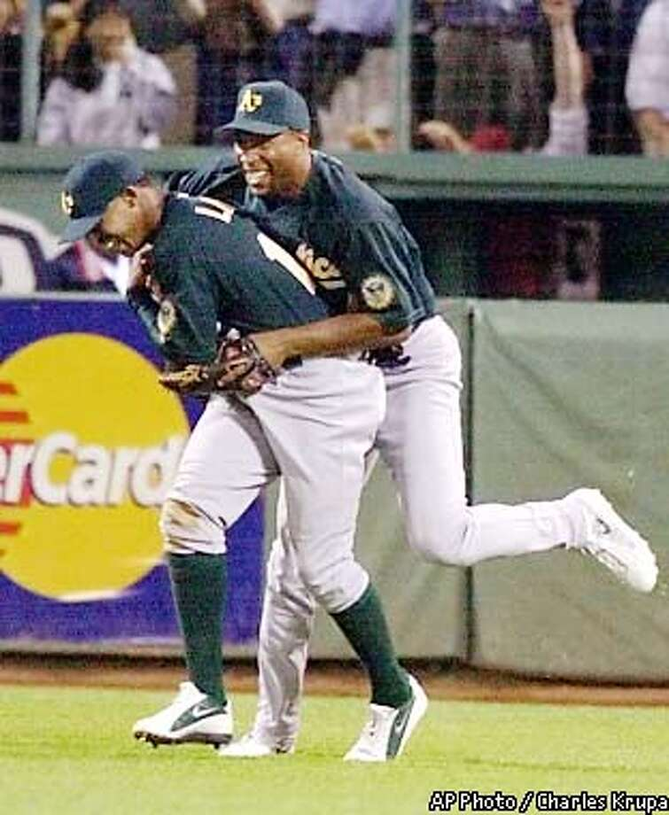 Oakland Athletics center fielder Terrence Long, left, is embraced by teammate Jermaine Dye after Long reached over the Boston Red Sox bullpen wall and robbed Red Sox batter Manny Ramirez of a three-run home run in the ninth inning to end the game at Fenway Park in Boston, Wednesday, Aug. 7, 2002. Dye belted a two-run, home run in the sixth inning which gave the Athletics the lead in the game. (AP Photo/Charles Krupa) Photo: CHARLES KRUPA