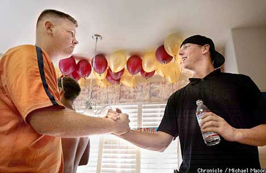 Liberty High teammate Matt Gaudinier, left, congratulates Chris Gruler during a draft party at Gruler's home in Brentwood. Chronicle photo by Michael Macor