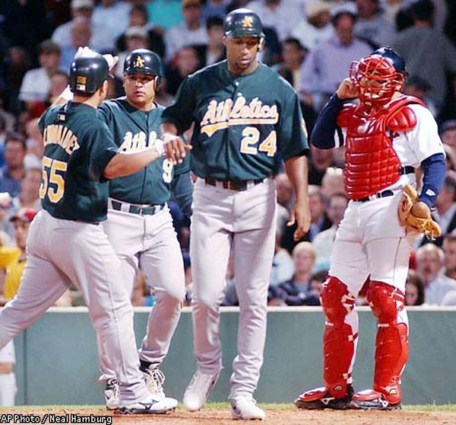 Boston Red Sox catcher Doug Mirabelli reacts at right as Oakland Athletics' Olmedo Saenz (9) is congratulated by teammate Ramon Hernandez (55) after hitting a three-run homer scoring Hernendez and Jermaine Dye (24) in fifth iinning action at Fenway Park in Boston Tuesday, August 6, 2002. (AP Photo/Neal Hamburg) Photo: NEAL HAMBERG