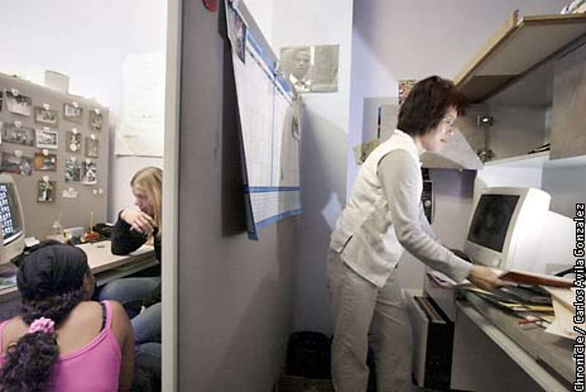 In Hui Lee, right, sets up her work study cubicle at Lifetime in Oakland, Ca., on Tuesday, June 25, 2002. Lee is in training through a welfare to work program. (BY CARLOS AVILA GONZALEZ/THE SAN FRANCISCO CHRONICLE)