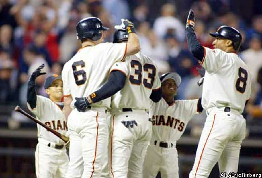 San Francisco Giants' Benito Santiago (33) is greeted by teammates J.T. Snow (6), Tom Goodwin (8) and two bat boys after Santiago's game-winning infield single in the 10th inning against the Chicago Cubs, Wednesday, Aug. 7, 2002, in San Francisco. The Giants won 4-3. (AP Photo/Eric Risberg) Photo: ERIC RISBERG