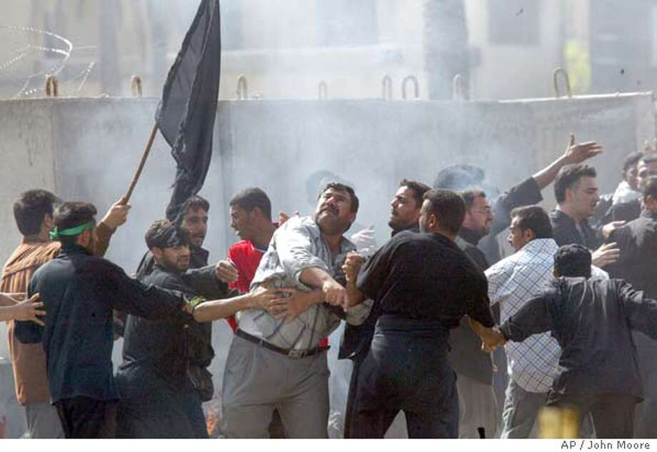 An angry mob of Iraqis throw rocks at US troops after retreating back to their camp following a series of explosions near a Shiite mosque in Khadimiya in Baghdad, Iraq Tuesday March 2, 2004. The US troops, who rushed to the scene, retreated after angry Iraqis vented their anger on them. Multiple explosions rocked the capital and the Shiite holy city of Karbala Tuesday killing scores of people and injured many others as the Shiites marked the final day of Ashoura, the ten-day mourning of the death of one of their important saints Imam Hussein. (AP Photo/John Moore) Photo: JOHN MOORE