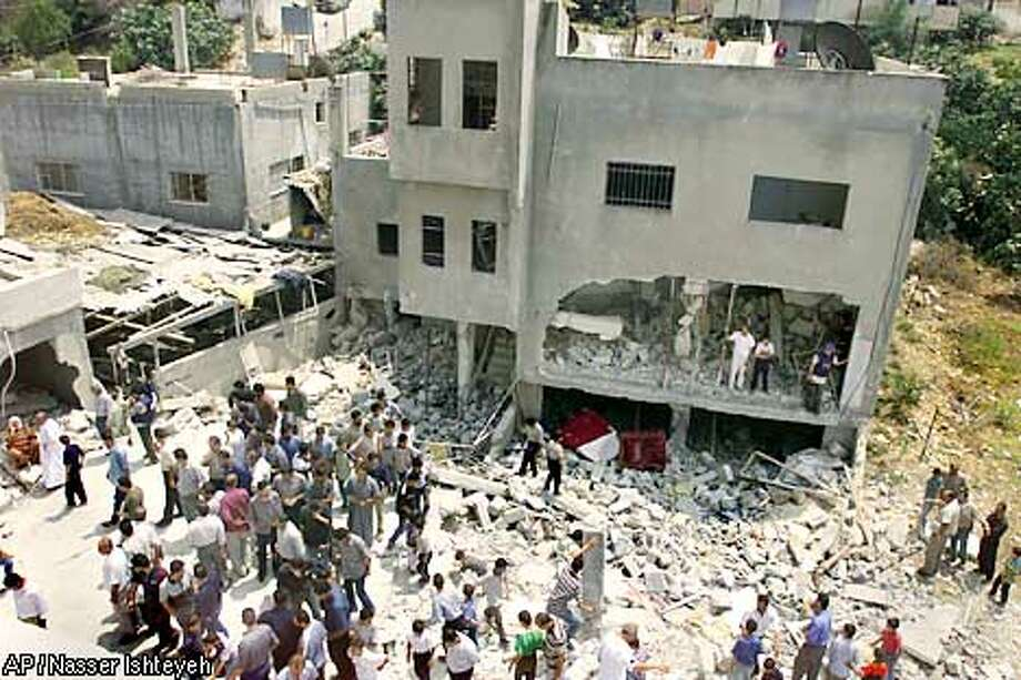 Palestinians climb to survey the destruction after the Israeli army blew up the house of Assem Rihan in the village of Tel, outside of the West Bank town of Nablus, Sunday, Aug. 4, 2002. Rihan was killed by Israeli soldiers after he was said to have opened fire on a Jewish settler bus on a road near Tel several months ago. His house was destroyed as part of a new policy of demolishing homes of suicide bombers and other militants. (AP Photo/Nasser Ishteyeh) Photo: NASSER ISHTEYEH