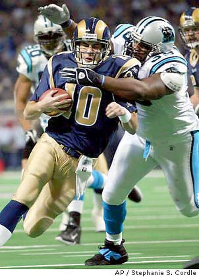 St. Louis Rams quarterback Marc Bulger, left, is tackled by the Carolina Panthers Brentson Buckner, right, during the second quarter of play in St. Louis on Saturday afternoon. (AP Photo by Stephanie S. Cordle) Photo: STEPHANIE S. CORDLE