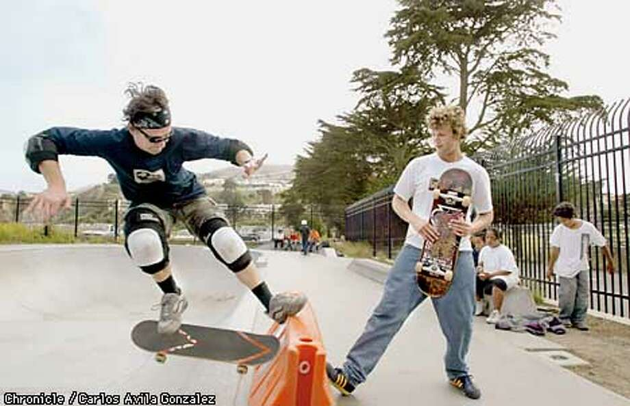 Mike Gulizia left, performs a maneuver as Leif Veimoen holds a barrier at the Crocker-Amazon Skate Park on Thursday, August 1, 2002. It took almost two years for the city to complete the Crocker-Amazon Park skate park, and the facilities are substandard according to many of the people who use them. Skateboarders are migrating to different cities for better conditions. (BY CARLOS AVILA GONZALEZ/THE SAN FRANCISCO CHRONICLE) Photo: CARLOS AVILA GONZALEZ