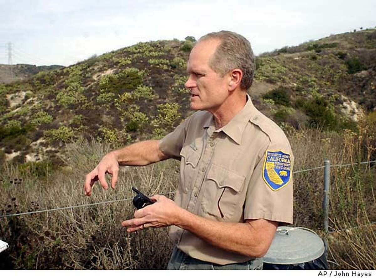 Doug Updike, describes how a mountain lion attacks its prey near the entrance to a trail of the Whiting Ranch Wilderness Park in an unincorporated area of Orange County Friday, Jan. 9, 2004, following a pair of mountain lion attacks in the area. (AP Photo/John Hayes)