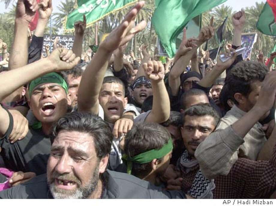 Shiites and Sunni Muslims shout slogans during a protest at the Al-Khadum Mosque in Kazimiya district in Baghdad Wednesday March 3, 2004 to show solidarity in the wake of Tuesday's suicide attacks in the capital as well as in the holy city of Karbala which killed at least 150 worshippers and injured hundreds more. (AP Photo/Hadi Mizban) Photo: HADI MIZBAN
