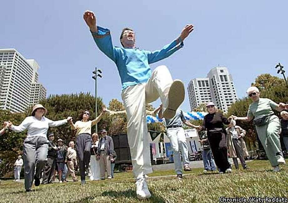 PHOTO BY KATY RADDATZ--THE CHRONICLE  Fair celebrating Israel's 54th birthday, at yerba Buena Gardens, in San Francisco. SHOWN: Allen King, a teacher of folk dance, teaches a sunlit and happy crowd the dance invented for Isreal's 25th birthday. Photo: KATY RADDATZ