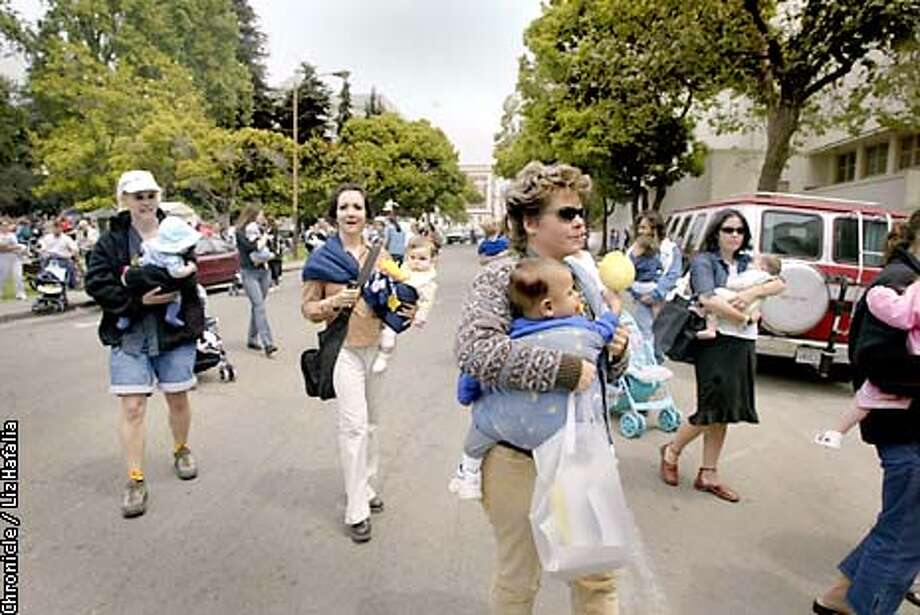 More than 650 breast feeding mothers gathered in an effort to beat Australia's world record for most women simultaneously breast feeding. Cece Sellgren (front) with her 15 month year old, Christopher, heading to the Community Theater in Berkeley.  (PHOTOGRAPHED BY LIZ HAFALIA/THE SAN FRANCISCO CHRONICLE) Photo: LIZ HAFALIA