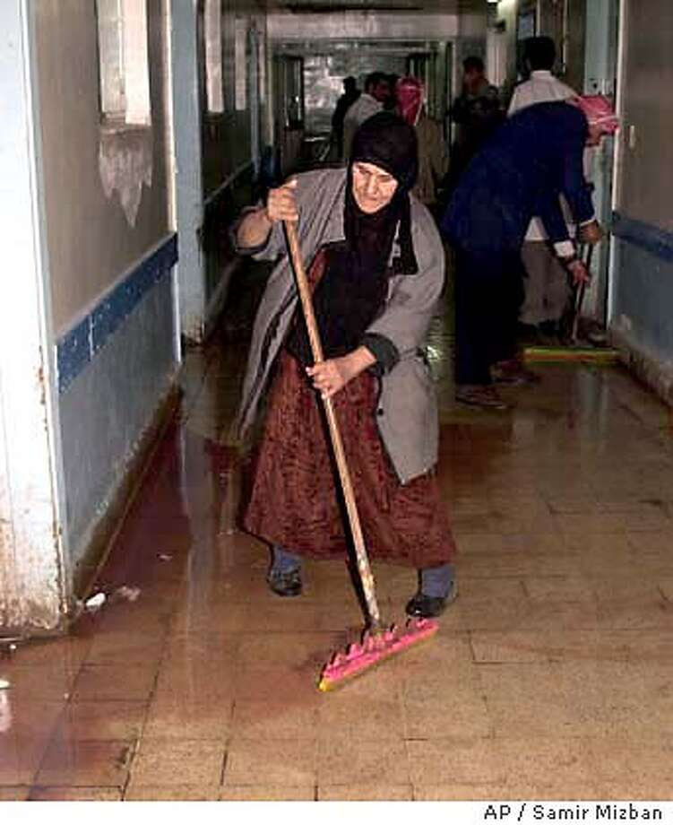 Staff clean the floor of blood in a hospital in Baqouba, Iraq Friday Jan. 9, 2004 after an explosion ripped through the street in the town outside a Shiite Muslim mosque after midday prayers, killing up to five people and wounding dozens of others. It was not immediately clear what caused the blast. (AP Photo/Samir Mizban) Photo: SAMIR MIZBAN