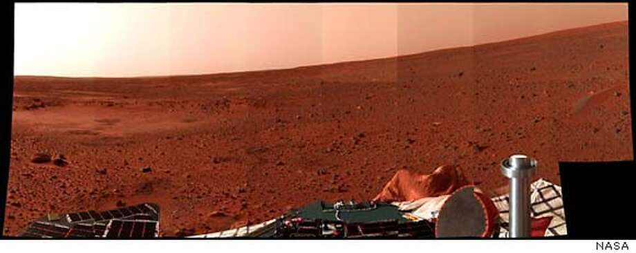 """This latest color """"postcard from Mars,"""" taken on Sol 5 by the panoramic camera on the Mars Exploration Rover Spirit, looks to the north, in this image released January 8, 2003. The apparent slope of the horizon is due to the several-degree tilt of the lander deck. On the left, the circular topographic feature dubbed Sleepy Hollow can be seen along with dark markings that may be surface disturbances caused by the airbag-encased lander as it bounced and rolled to rest. A dust-coated airbag is prominent in the foreground, and a dune-like object that has piqued the interest of the science team with its dark, possibly armored top coating, can be seen on the right. The pictures were released by the Jet Propulsion Laboratory in Pasadena, California, Janaury 8, 2004. EDITORIAL USE ONLY /NASA/JPL/Cornell University/Handout Photo: HO"""