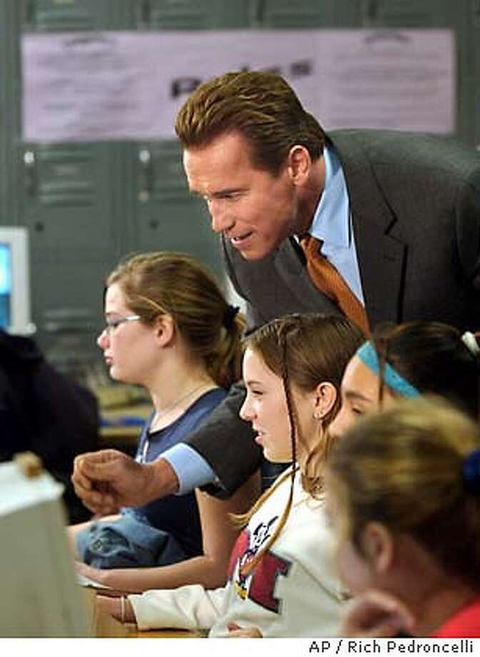 California Gov. Arnold Schwarzenegger looks over the shoulder of eighth grader Faith Lundgren,13, third from right in white sweater, as she works on a computer at the Sutter Middle School in Sacramento, Calif., Thursday, Jan. 8, 2004. Schwarzenegger toured the school before announcing that he had reached an agreement with educators on next year's budget proposal. (AP Photo/Rich Pedroncelli, Pool) Photo: RICH PEDRONCELLI