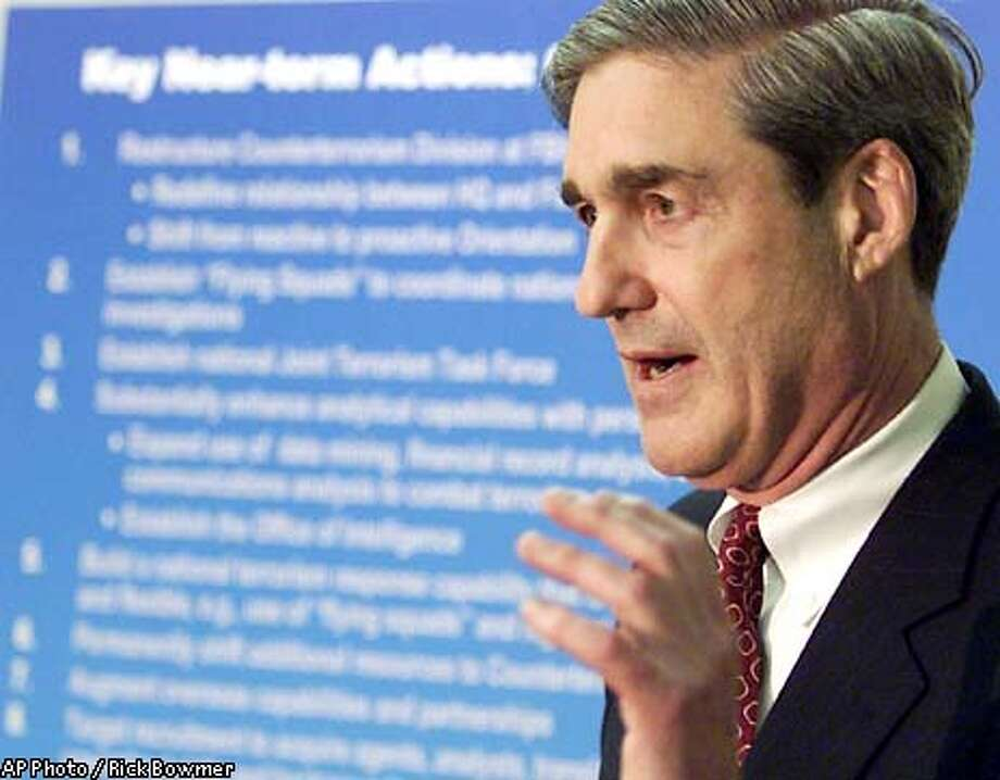 FBI Director Robert Mueller talks about the reorganization of the FBI during a news conference at FBI headquarters in Washington Wednesday, May 29, 2002. Mueller said one change will require the bureau to hire some 900 new agents nationwide by September, mostly specialists in computers, foreign languages and sciences. (AP Photo/Rick Bowmer) Photo: RICK BOWMER