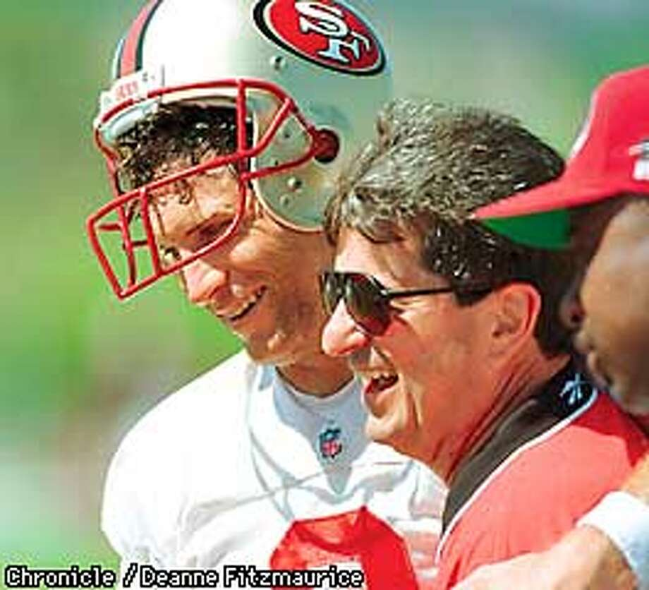 Steve Young shares a laugh with 49er Pres. CArmen Policy as he arrives at training camp in Rocklin to announce the signing of a new contract. CHRONICLE PHOTO BY DEANE FITZMAURICE