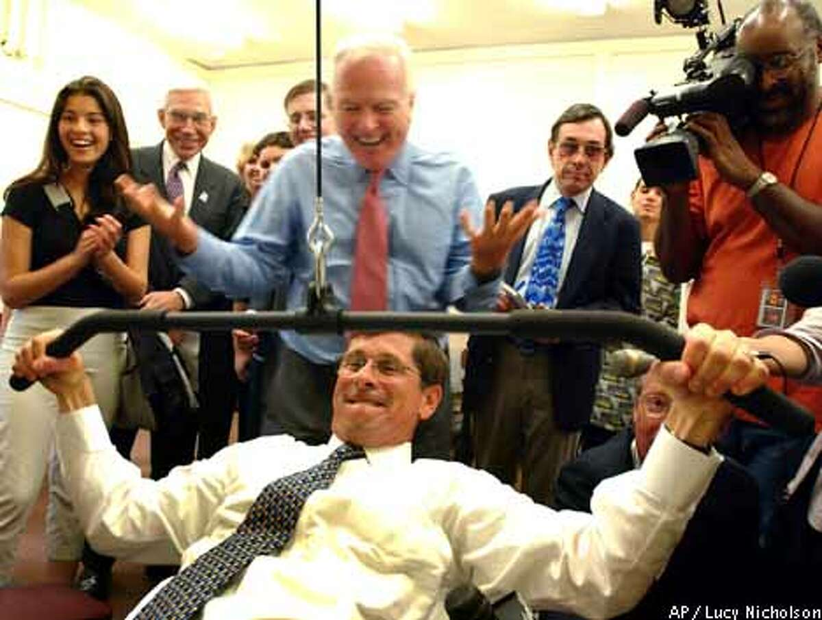 Bill Simon tries to lift weights as defeated GOP candidate Richard Riordan cheers him on at a gym dedication at a Los Angeles high school. Associated Press photo by Lucy Nicholson