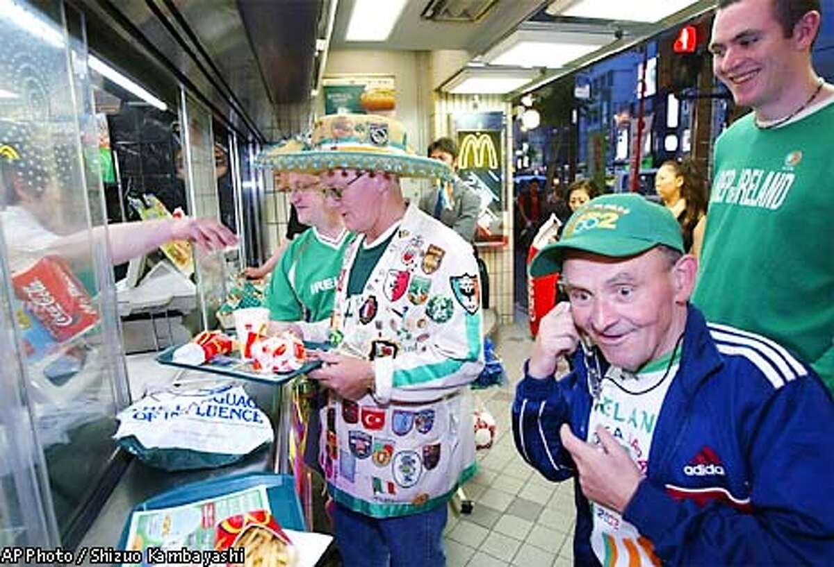 Fans of the Irish World Cup soccer team, from left, Jacko Treasy, Joe McDermott, Tommy Keating and Brendan O' Sullivan, in the team's green uniform, line up at McDonald's restaurant counter in Tokyo's Roppongi entertainment district Thursday, May 30, 2002, eve of the opening of the 2002 World Cup Korea/Japan. Ireland competes in Group E against Germany, Saudi Arabia and Camerron in Japan. (AP Photo/Shizuo Kambayashi)