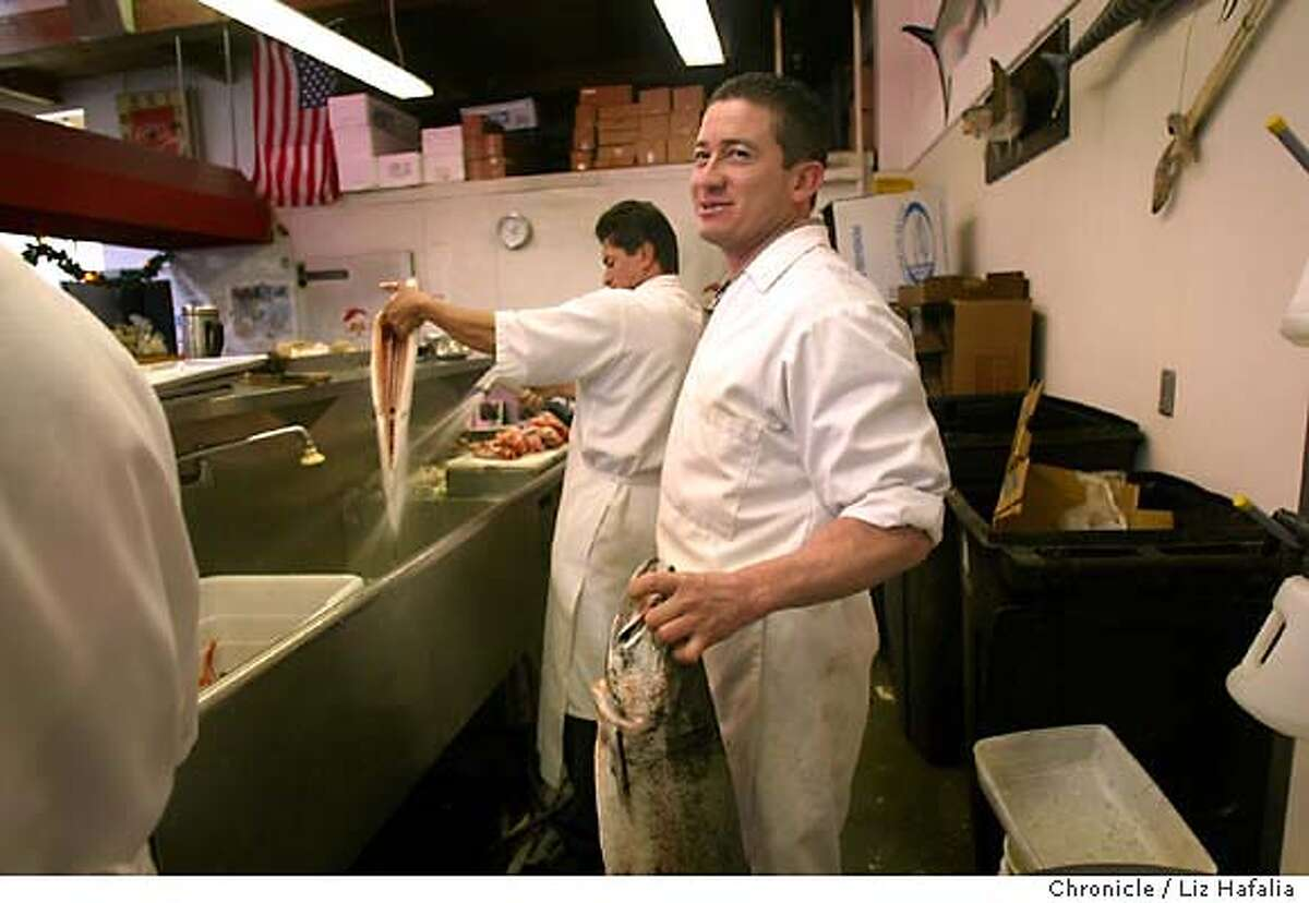 George Soto holding a wild Columbia salmon (front) while a farmed salmon (left) is being washed at the Mission Market fish counter. Shot on 1/8/04 in San Francisco. LIZ HAFALIA / The Chronicle