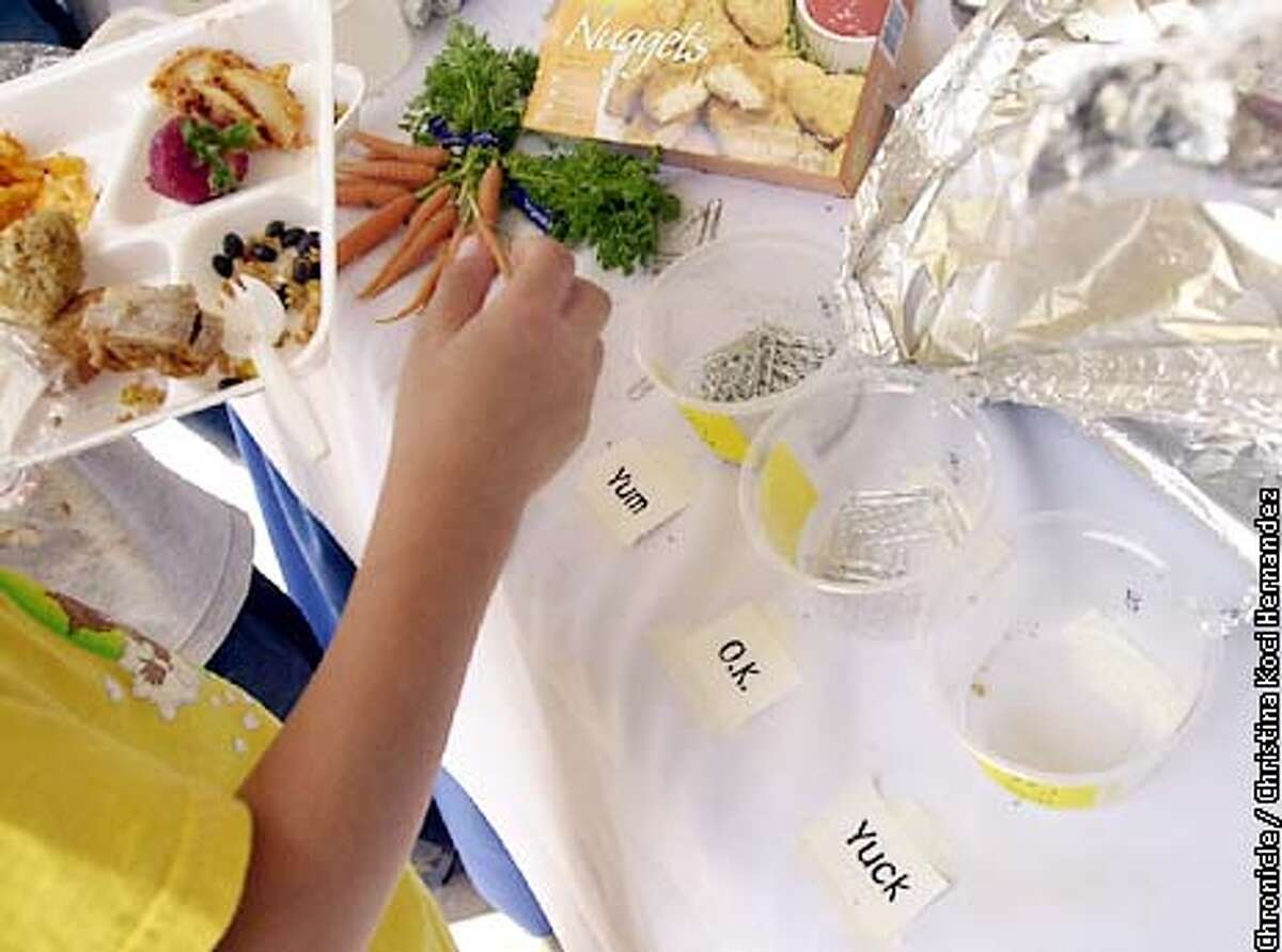 CHRISTINA KOCI HERNANDEZ/CHRONICLE A kid samples food with the rating system on the table, yum, ok or yuck. Kids at Ohlone Elementary School in Palo Alto sample organic foods that are proposed to replace standard cafeteria food in a pilot program.