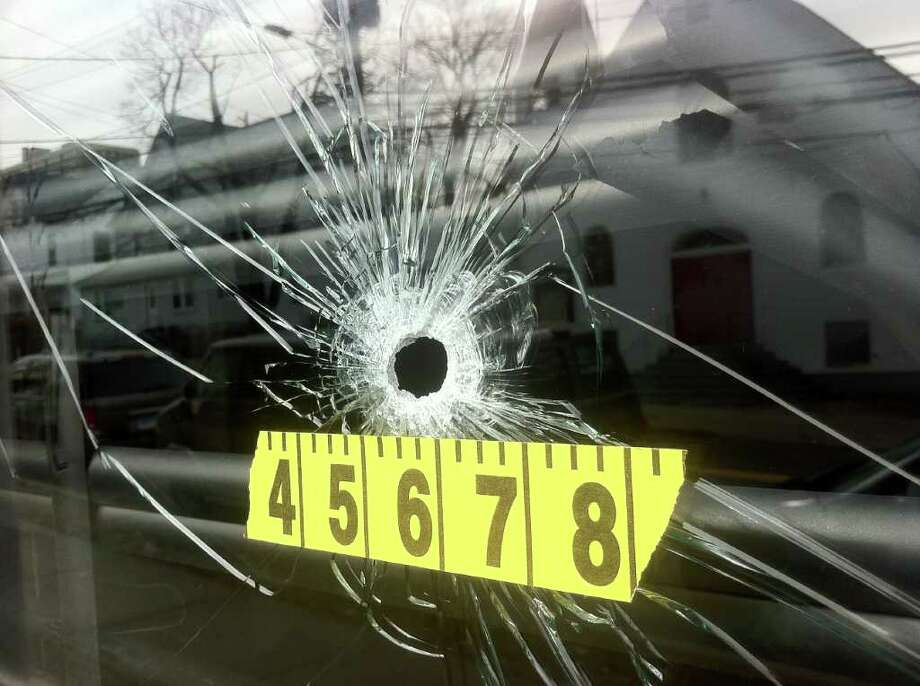 A bullet hole in the window of Cut Masters Barbershop at 91 Richmond Hill Ave. in Stamford, where two city men were shot Saturday night. Photo: Keelin Daly/staff Photo