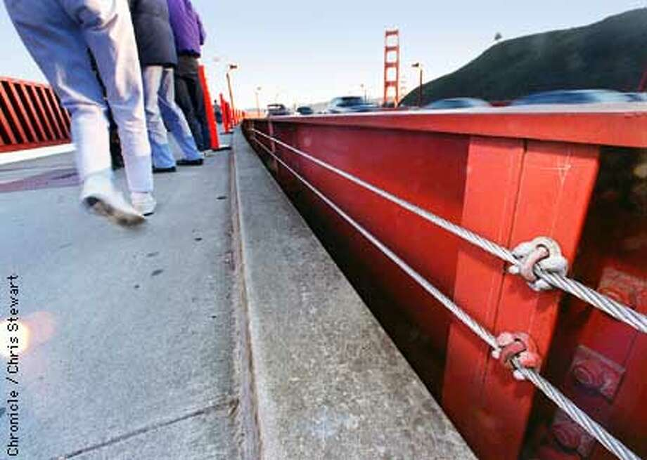 Pedestrians stroll past newly installed safety cables on the Golden Gate Bridge. The cables narrow the nine inch gap which separates the sidewalk from the roadway barricade to prevent a repeat of the death Sunday of a two-year-old girl who fell through the gap and to the ground 170 feet below. Only 20 to 30 feet of cable has been installed at this point. SAN FRANCISCO CHRONICLE PHOTO BY CHRIS STEWART Photo: CHRIS STEWART