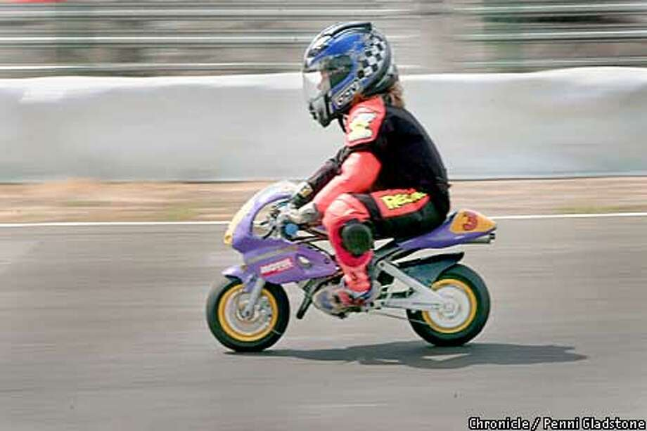 ConfidentElena Myers age 8 yrs races past. minimoto racing in STOCKTON, at the Motorplex Park, San Joaquin County Fairgrounds. the west coast minimotto club has about 30 members from the Bay Area, So. Cal and Oregon participating in their first race today.  PHOTOGRAPHY BY PENNI GLADSTONE Photo: PENNI GLADSTONE