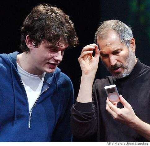 Apple CEO Steve Jobs, right, examines his company's new product, the iPod mini, along with musician John Mayer at the Macworld Conference and Expo in San Francisco Tuesday, Jan 6, 2004. (AP Photo/Marcio Jose Sanchez) Photo: MARCIO JOSE SANCHEZ