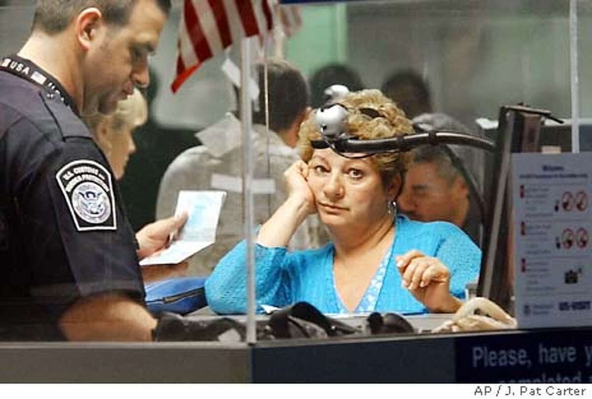 A woman traveling from South America watches as her data comes up on a computer screen after she was fingerprinted and photographed Monday, Jan. 5, 2004 as she arrived at Miami International Airport. The digital data has to match data from her checked passport. (AP Photo/J. Pat Carter)