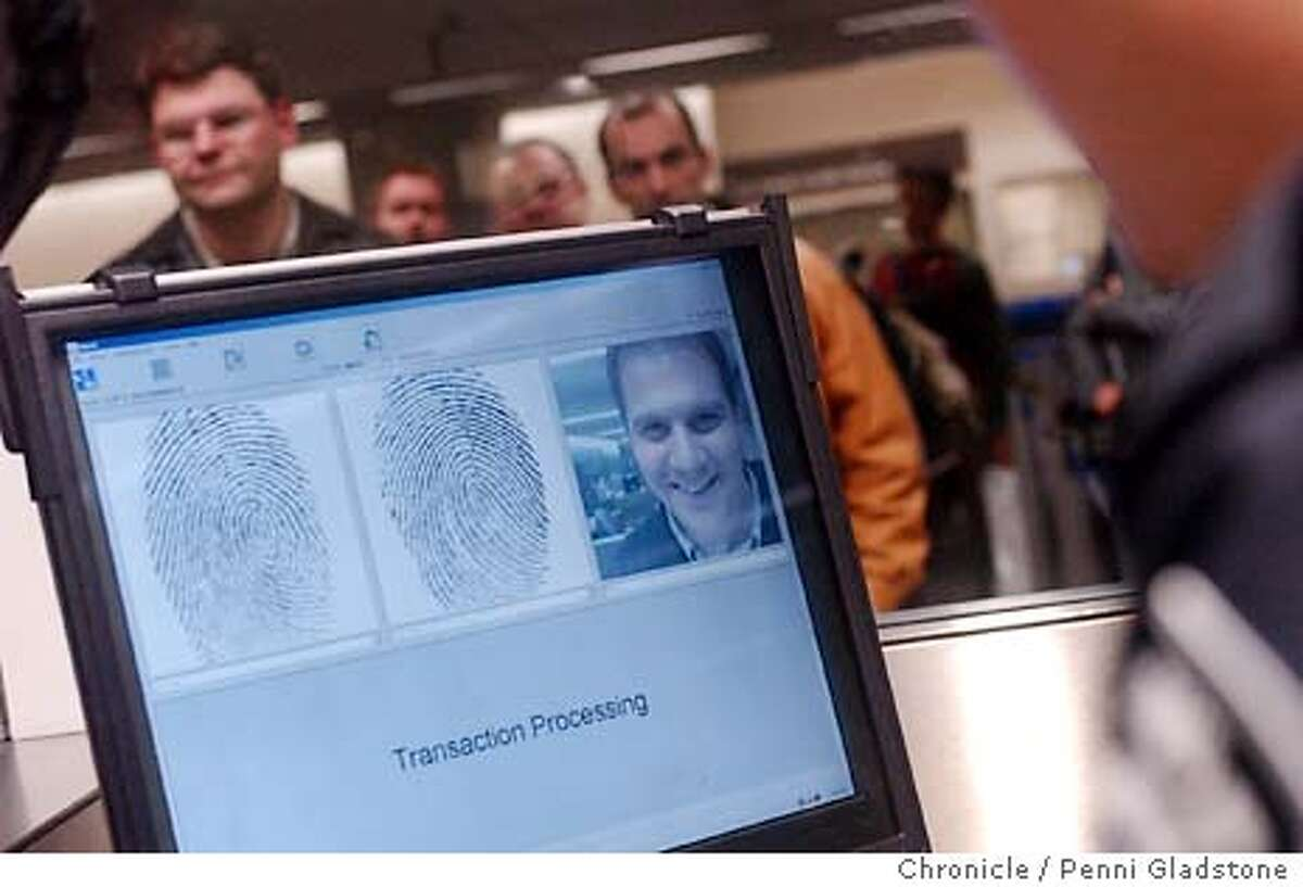 SECURITY052_pg.jpg new security at sf airport in immigration show a picture of this man who just arrrive from Europe and his finger prints just taken. Passengers wait in line behind to go thru immigration. 1/5/04 in San Francisco. PENNI GLADSTONE / The Chronicle