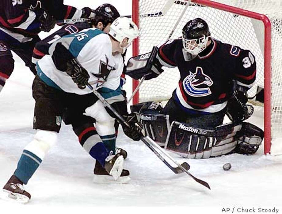 Vancouver Canucks goalie Dan Cloutier makes a save on a shot from San Jose Sharks' Wayne Primeau as Canucks' Brendan Morrison defends during the first period of NHL action in Vancouver, British Columbia, Monday Jan. 5, 2004. (AP Photo/Chuck Stoody) Photo: CHUCK STOODY