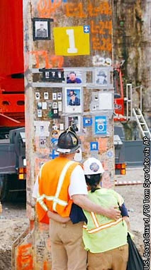 Unidentified rescue workers at Ground Zero embrace while looking at the last beam of the World Trade Center, Tuesday, May 28, 2002, in New York. The last piece of steel left standing in the demolished World Trade Center will be cut down Tuesday evening as ground zero workers, victims' families and the city prepare for several ceremonies marking the end of the unprecedented recovery effort. (AP Photo/U.S. Coast Guard, PO Tom Sperduto, HO) Photo: PO TOM SPERDUTO