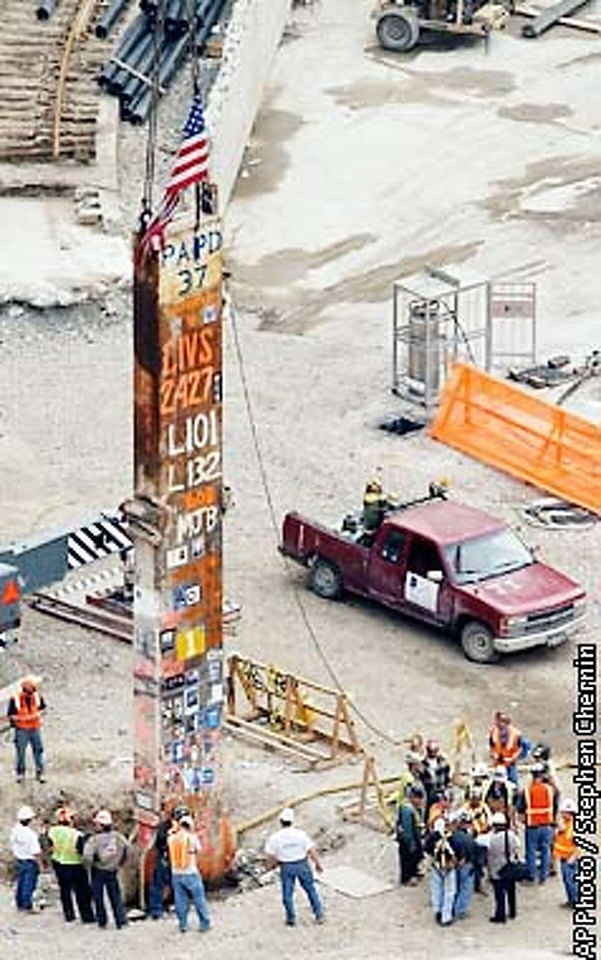 Workers gather around the last steel beam left standing at the World Trade Center disaster site Tuesday, May 28, 2002 in New York. The beam is set for demolition Tuesday evening in the first of a series of ceremonies marking the end of the sorrowful, 8 1/2 month cleanup. (AP Photo/Stephen Chernin)