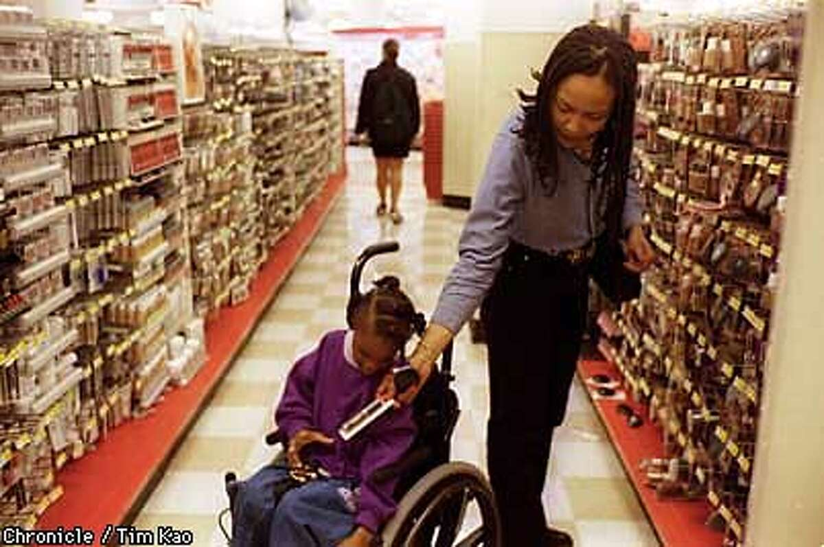 =Iva Rochell passes an eye liner brush for her daughter Venassa, 9, to hold in the Woolworth downtown. Rochell, a resident of downtown SF, does her odds-and-ends shopping here about twice a week. photo by Tim kao/the chronicle