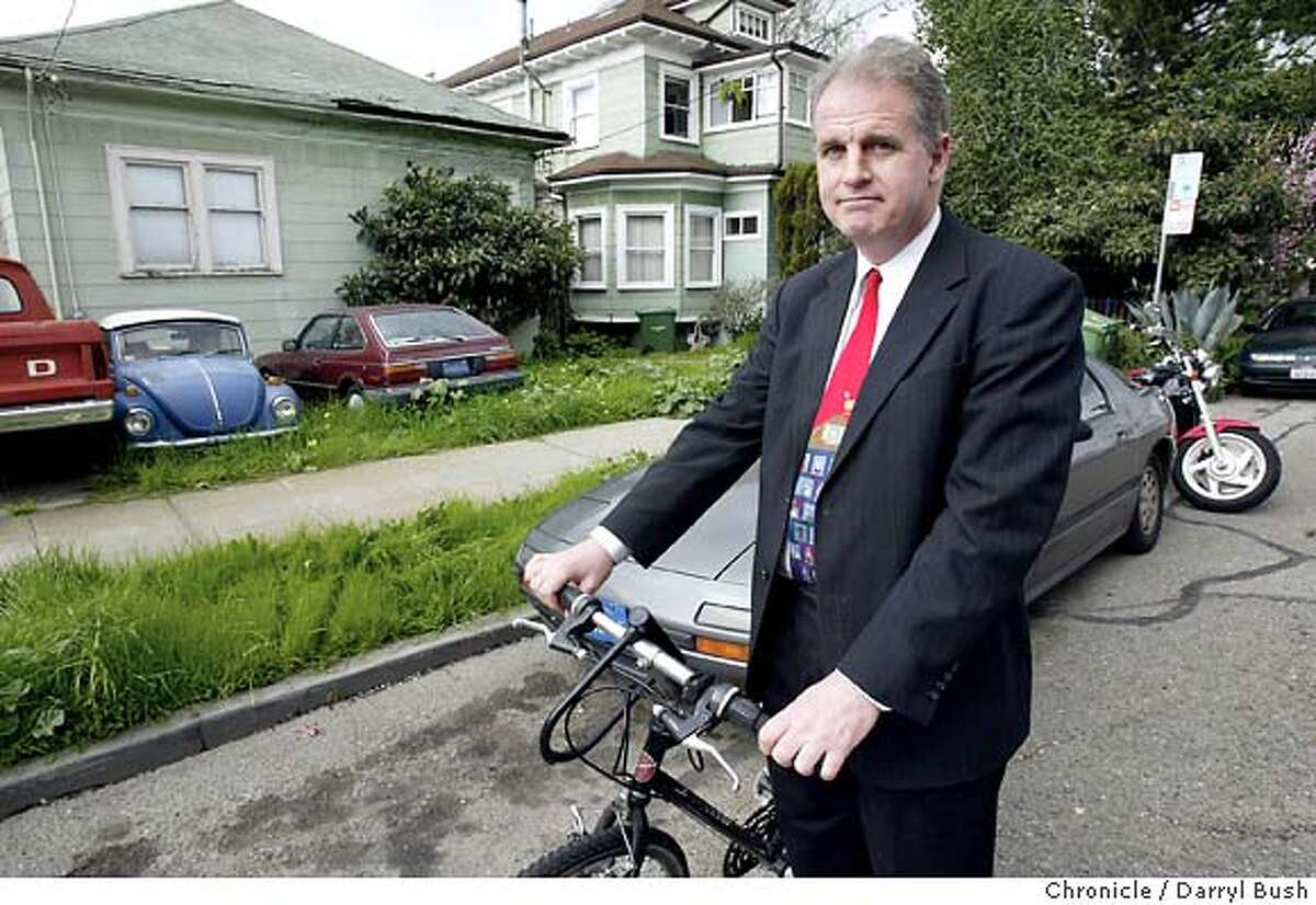Berkeley councilman Kriss Worthington rides his bike on Grant Street, next to a house that has cars in the front yard. A new car tax is being proposed in Berkeley for residents who own multiple cars. Event on 2/20/04 in Berkeley. Darryl Bush / The Chronicle