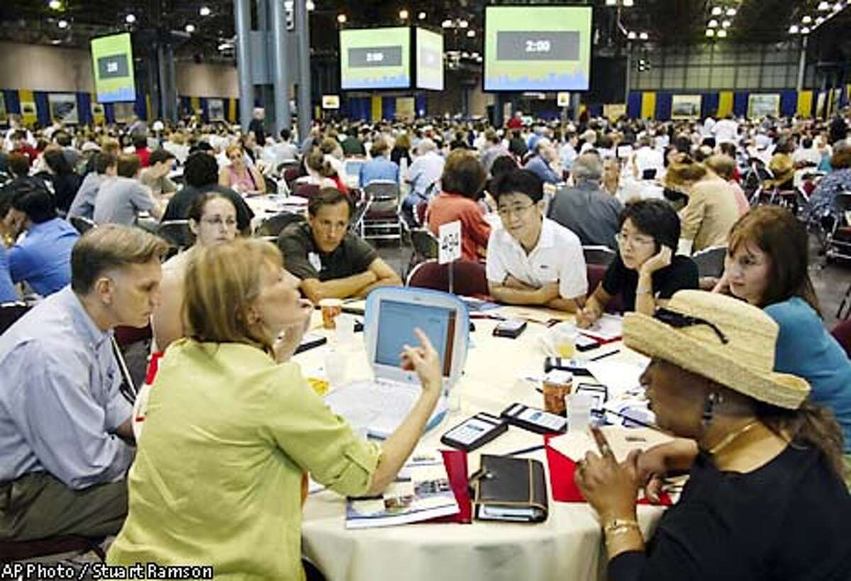 Participants of table no. 494 watch their facilitator Sharon Jones, foreground second from left, explain procedure at a historic 21st century town hall meeting to consider the World Trade Center site plans presented by the Lower Manhattan Development Corporation and the Port Authority of New York and New Jersey, July 20, 2002, in New York. Also to be discussed is the creation of a memorial to the victims of Sept 11 and other priorities for the rebuilding process in downtown New York. (AP Photo/ StuartRamson)